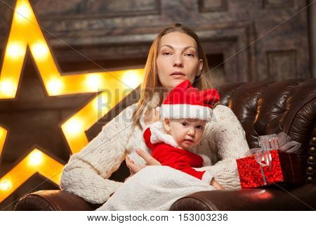 Portrait of happy mother and litle baby in santa's hats.