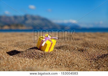 One yellow gift box on a beach