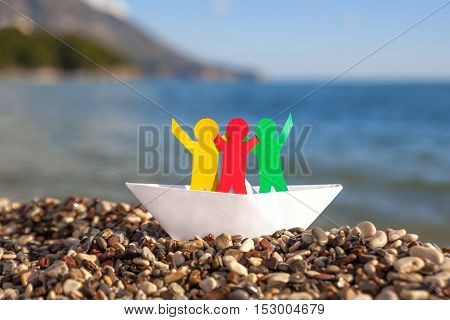 Multicolored paper people in white paper boat on a sand beach