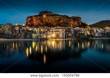 View on habour and old houses in Cefalu at night, Sicily. Beautiful townscape of old italian town. Travel photography.