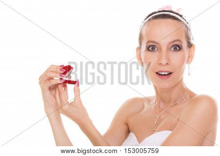 Excited happy bride holding opening engagement ring box. Surprised woman in white wedding dress isolated on white background.