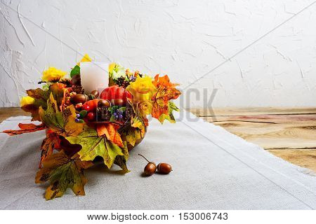 Thanksgiving centerpiece with decorated candle and silk fall leaves . Thanksgiving background with fall decor. Fall background. Copy space.