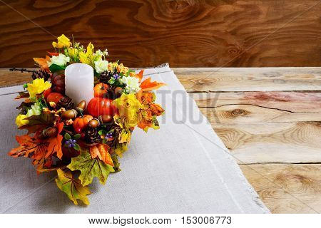 Thanksgiving centerpiece with artificial fall leaves. Thanksgiving background with fall decor. Fall background. Copy space.