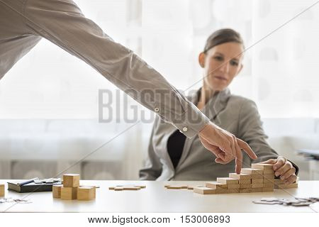 Worker watching someone use fingers on blocks in office for concept about progress and goals.