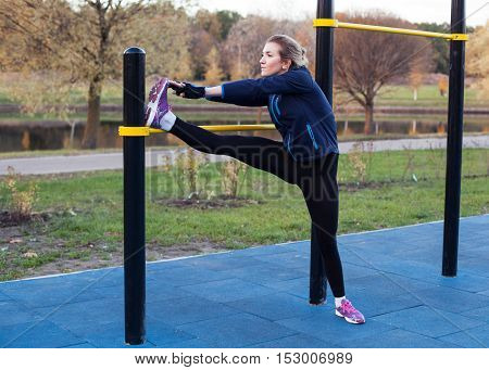 Young fitness woman throwing the foot on the bar and stretching the leg outdoors