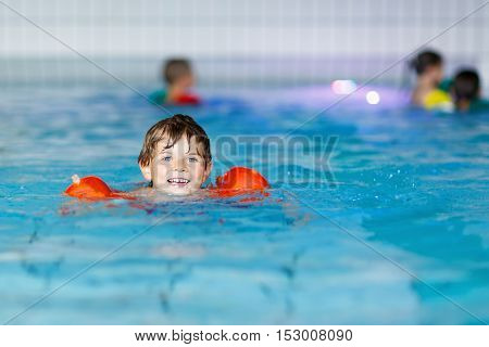 Active adorable little preschool kid boy with swimmies learning to swim in an indoor pool. Active and fit leisure for children. Happy child making sports and learning safe swimming.