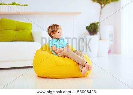 Cute Kid Having Sitting On Yellow Bean Bag At Home