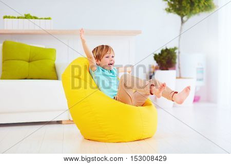 Excited Kid Having Fun, Sitting On Yellow Bean Bag At Home