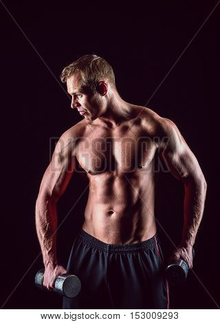 Muscular, strong and sexy man with dumbbells on black background.