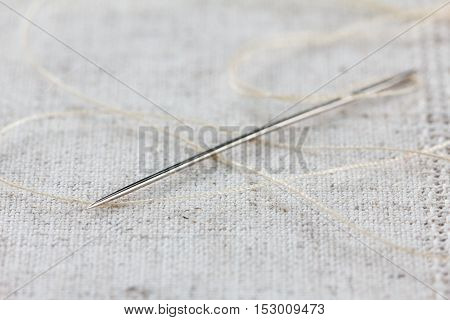 Needlework and handmade linen fabric with needle and thread