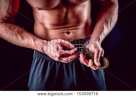 Muscular man fasten lifting belt over dark background.