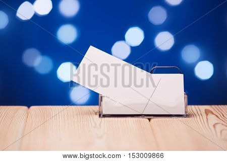 Professional blank business cards in holder stands on wooden table on a abstract blue background.