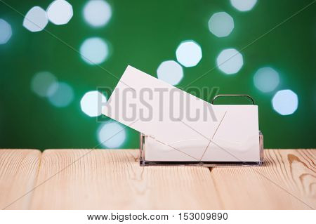 Professional blank business cards in holder stands on wooden table on a abstract green background.