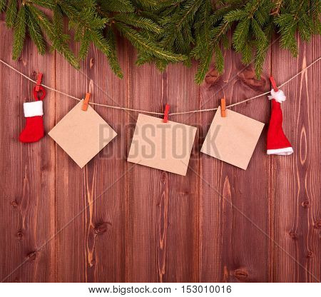 Fir tree branches, Christmas decor  and empty blank paper on a wooden background. Copy space for text. Christmas and New Year.