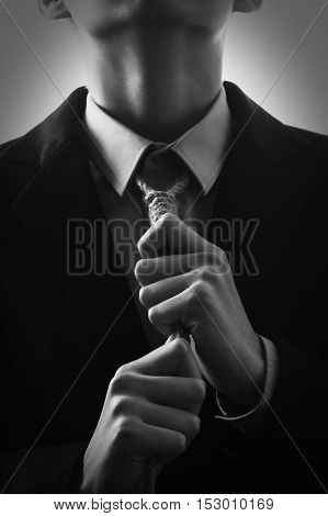 Man in a suit about to hang himself in the noose