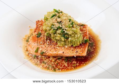 Grilled salmon fillet with avocado mash on white plate