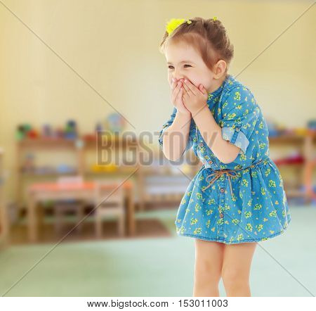Cute little girl in a short blue dress terrified has closed hands the person. Close-up.Against the background of a child's room , concept of education and family values.