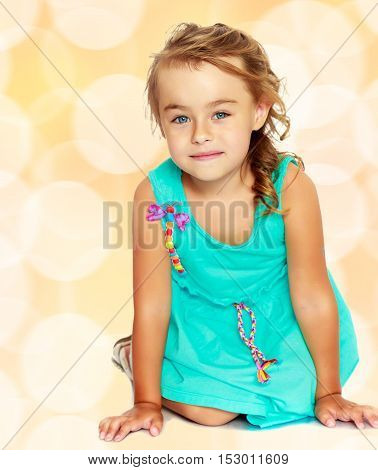 Delicate little blonde girl, dressed in a blue dress standing on her knees. She looks directly into the camera.Brown festive, Christmas background with white snowflakes, circles.