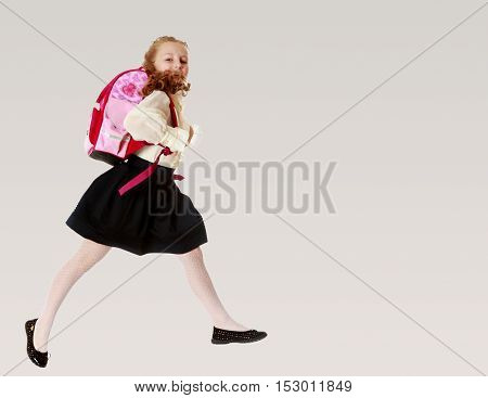 Pretty little girl schoolgirl in white blouse and black skirt to hurry to school. She jumps over the obstacle.On a gray background.