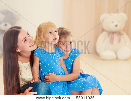 Beautiful young mother with her two daughters. All look up.In the background children's room where the sitting Teddy bear.
