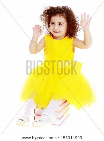 Cute little curly girl in a bright yellow elegant dress sitting on a stack of books. She gestures with her hands.Isolated on white background.