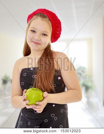 Cute little girl in fancy dress, holding a green Apple. Close-up.In the room with large, bright Windows.