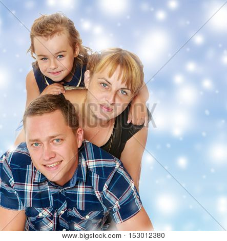 Cheerful young family of three. Mother and daughter lying on dad's back.Blue Christmas festive background with white snowflakes.