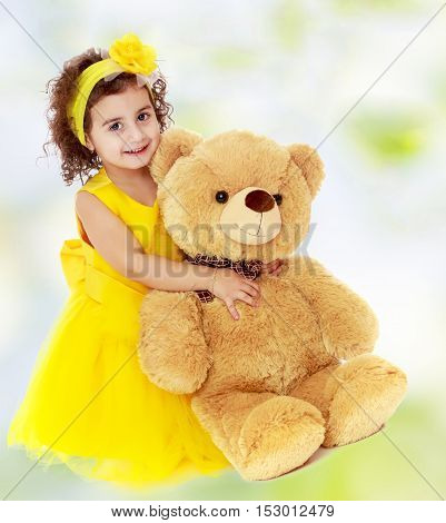 Joyful little girl in a yellow dress and bow on her head sitting on the floor. Girl hugging a big Teddy bear.white-green blurred abstract background with snowflakes.