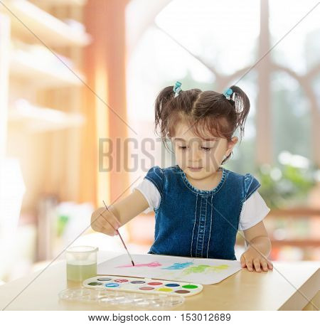 Cute little girl draws with watercolors on a sheet of white paper . Girl sitting at the table.In a room with a large semi-circular window.