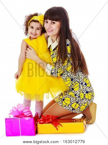 Beautiful young mother and her cute little daughter , embracing, surrounded by Christmas gifts.Isolated on white background.