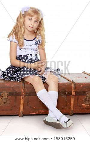 Tired little girl with long blonde ponytails on her head, sitting on the old road suitcase-Isolated on white background