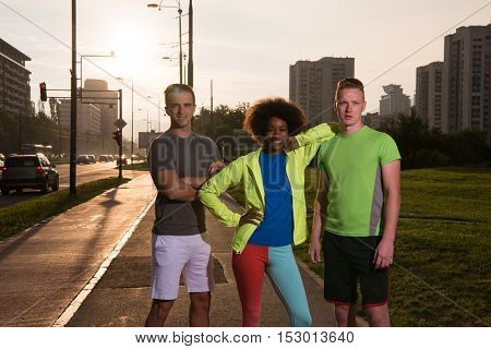 Portrait of multi-ethnic group of young people on the jogging beautiful summer evening as the sun sets over the city