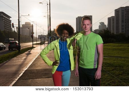 portrait of a young African American beautiful woman and a young man jogging in the city
