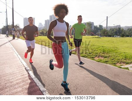 multiethnic group of young people on the jogging beautiful morning as the sun rises in the streets of the city