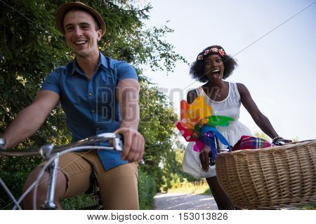 a young man and a beautiful African American girl enjoying a bike ride in nature on a sunny summer day