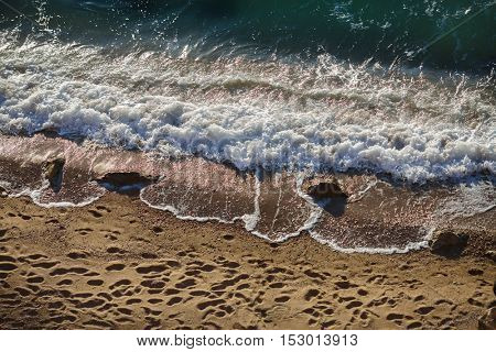 Waves lapping on the sandy beach and footprints
