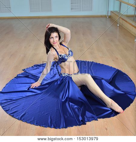 Young Beautiful Sexy Belly dancer in arabic costume dancing on a floor.