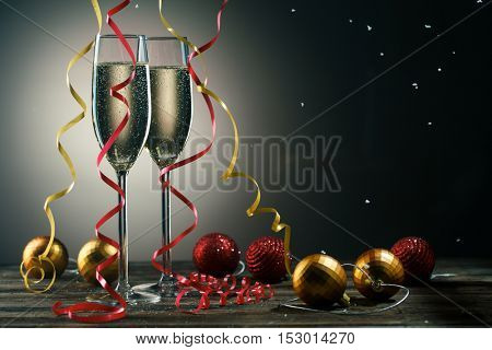 Two glasses with sparkling champagne, snowflakes and Christmas balls