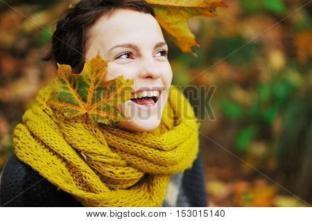 Fun portrait of a young laughing girl in a knitted scarf with maple leaves in her hair