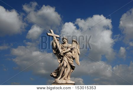 Beautiful angel statue holding a cross with heavenly sky from Sant'Angelo Bridge in the historic center of Rome (17th century)