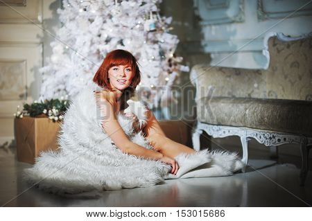 Charming smiling girl in a white fur cloak sitting beside a decorated Christmas tree New Year