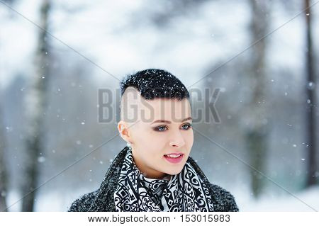 Portrait of a charming gray-eyed girl with snowflakes on short hair with a beautiful scarf on the background of falling snow in winter Park.