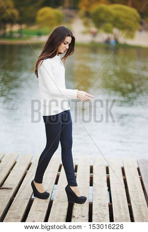Slender long haired brunette in white sweater black leggings and high-heeled shoes is on a wooden bridge near the river in the autumn Park