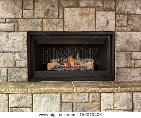Burning natural gas fireplace surround by stone