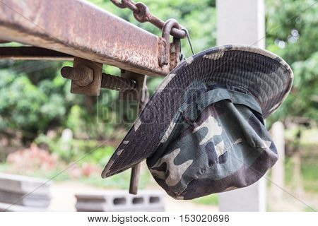 Military camouflage hat hanging on a matal in the forest background