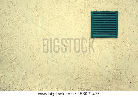 Old ventilation grille with bars on a grungy building, white wall