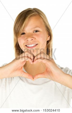 Young girl forming heart symbol with her hands over white background