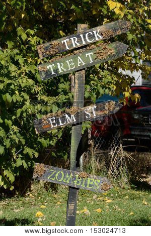 Homemade Halloween street sign decoration pointing the way to Trick, Treat, Elm Street and Zombies