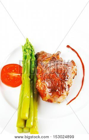 roast meat served with asparagus on white dish