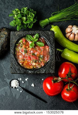 Traditional Latin American mexican Tomato sauce salsa, chilean chancho en piedra in stone mortar and ingredients tomatoes, chile, garlic, onion, sea salt on dark slate stone background. Top view